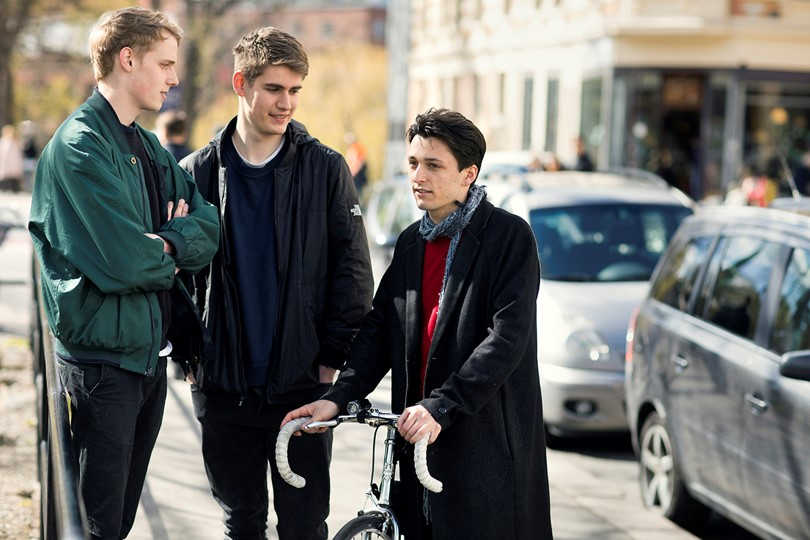 Three male students with a bicycle